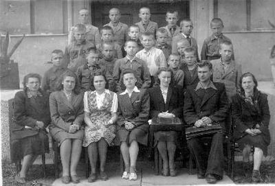 Grupinė. Biržų II vidurinės mokyklos mokytojai ir mokiniai prie gimnazijos pastato. Sėdi iš kairės: lietuvių kalbos mokytoja Gelažnikienė, x, anglų k. mokytoja Jadvyga Šušytė - Pančkauskienė, x, rusų k. mokytoja Nastopkaitė - Januševičienė, fizikas Banys, piešimo mokytoja A. Sirutytė. II eil.: 1 - mokinys Džiuvė (vėliau - Obelaukių kolūkio pirmininkas), 2 - Apinys, paskutinis - Galvanauskas.