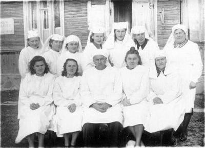 Grupinė. Biržų ligoninės medicinos personalas prie medinio ligoninės pastato (prie ežero). Sėdi iš kairės: gydytojai Regina Bajoriūnienė, Kuginytė (fiziatrė), Daniūnas, Anastazija Kepalaitė - Balčiauskienė, seselė Kochlova. Stovi: med. seserys Aldona Baliūnienė, Balčiūnienė, Mintautienė, akušerė, dirbusi med. seserimi Gilienė (išvažiavo į JAV), Mačiukienė (vyras - JAV), x (vyras dirbo milicijoje), Laučiūnienė.