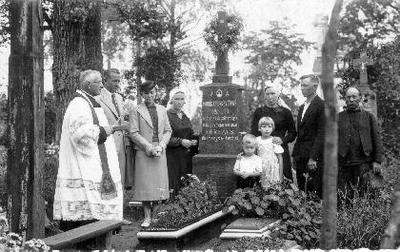 Siužetinė. Prie Monikos Penkevičienės kapo Veliuonos kapinėse iš kairės stovi: kunigas, Pranas ir Monika Lembertai, Marytė Eimutytė - Cvirkienė, Domicėlė Kazanovienė, Kazimieras Eimutis, x. Užrašas ant paminklo: A. A./ Monika Penkevičienė /1927 .II. 19. / Viešpatie būk gailestingas / mūsų gerajai motinai / Nuliūdę vyras / dukterys ir žentai. Monikos Penkevičienės vyras Jonas Penkevičius. Penkevičiai gyveno pasiturinčiai, Kaune turėjo du namus.