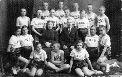 Grupinė. Biržų gimnazijos muštuko (beisbolo) ir orinio (tinklinio) komandos. Centre mokytojai Vilkickai. Pirmoje eilėje iš kairės: trečia - Lilija Tuomenaitė - Šidagienė, antroje eilėje pirma - Irena Sakalauskaitė - Venckienė, A. Nasovaitė, šešta - Birutė Morkūnaitė. Trečioje eilėje antra - L. Kuginytė, Lilė Vasiliauskaitė, Budriūnaitė.