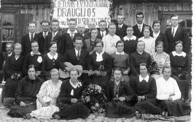 Grupinė. Lietuvos evangelikų krikščionių draugijos 25–ių metų sukaktuvių dalyviai prie savo maldos namų Biržuose. Centre sėdi vyras su gitara,viršutinėje eilėje, dešinėje, prie stendo stovi Mykolas Kvedaravičius.