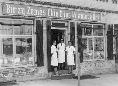 Siužetinė. Žemės ūkio draugijos parduotuvė Nr. 2 Kęstučio gatvėje. Vaizdas iš Kęstučio gatvės pusės. Tarpduryje stovi parduotuvės darbuotojos, iš kairės: Marija Užunarytė, Astrauskienė, Elena Velžytė. Apie 1989-1995 m. pastate veikė kavinė Akimirka, po to parduotuvė Armelina.