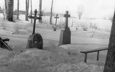 """Siužetinė. Kutrų kapavietė Mikeliškių kapinėse, Biržų raj. Matyti akmens kryžius (meistras Beriozovas, dirbtuvės buvo Biržuose, Kudirkos g.), ketinio kryžiaus jau nebėra, pakeistas. Prie paminklo paremta balieja . Nedrįsčiau tvirtinti, kad tai būtų plačiai paplitęs įdėklo pavadinimas, bet mano sąmonėje jis įstrigo nuo vaikystes. Matyt tai būta nepigaus kapo papuošalo, nes jų matydavosi nedaug. Vis tik cinkuota skarda anuomet dar buvo brangi. Matyt tai buvo laikina kapavietes aptvarkymo priemone, nes pastačius paminklus ir uždėjus antkapius, baliejos atsirasdavo greta paminklo. Kad būtų vaizdžiau futliarą sulyginsiu su daug kartu išdidinta maždaug 100x70x40 cm. per vidurį ištempta Nivėjos kremo dėže. Įstiklintas dangtis iš vieno šono turėjo du """"zoviesus"""", iš kito – kilpą spynelei (užrakinimui). Metaliniai vainikai, kartais kelių vainikų juostos, velionių nuotraukos buvo patalpinamos įdėkluose, o šis, specialiomis prilituotomis kilpomis pritvirtinamas prie kuolo pakeliant kažkiek nuo žemės, kad su ja nesiliestų. B. Januševičiaus inf."""
