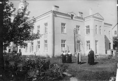 Siužetinė. Šv.Kazimiero seserų kongregacijos vienuolynas Vabalninke, pastatytas 1936 m. Pastatą bažnyčiai dovanojo amerikonas Sklėnys. Seserys kazimierietės šiame pastate buvo įkūrusios mergaičių amatų mokyklą ir vaikų darželį. Stovi iš kairės: seserys kazimierietės, x, kunigas M.Kirlys.Prie pastato - įdomios formos šulinys. Tarybiniais metais pastate buvo įsikūrę kultūros namai, biblioteka, atgimimo metais - muziejus. Matyti bažnyčios fasado dalis.