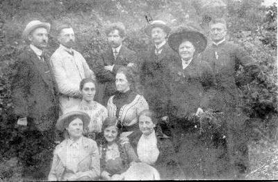 Grupinė. Grupė žmonių Papilyje. Pirmoje eilėje iš kairės sėdi: x, Marija Zinkevičiūtė, Olimpija Zinkevičienė. Antroje eilėje: Kotryna, Vanda Silvestravičiūtė. Trečioje eilėje: x, x, muzikas, pianistas, pedagogas Ignas Prielgauskas (1871-1956), x, x, kun. Mykolas Prielgauskas.
