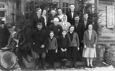 Grupinė. Knygnešys Kazys Gumbelevičius (1859–1941), apdovanotas Lietuvos nepriklausomybės dešimtmečio medaliu. Stovi centre, kartu su giminaičiais, prie savo namo Pasvalyje. Viršutinėje eilėje iš kairės pirmas Linkuvos gimnazijos mokytojas Paulius Gumbelevičius (?).