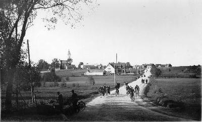 Siužetinė. Kelyje grupė dviračiais važiuojančių žmonių. Tolumoje Papilio miestelio (Biržų raj.) panorama ir katalikų bažnyčia. Vieškelis veda į plentą Rokiškis - Biržai. Kairėje stovi vyrai, šioje vietoje posūkis į dvarą. Kylant aukštyn kairėje - pieninė, dešinėje - tiltas per Rovėją ir kelias į Kvetkus. Prie pakelės kryžiaus keliukas į kapus.