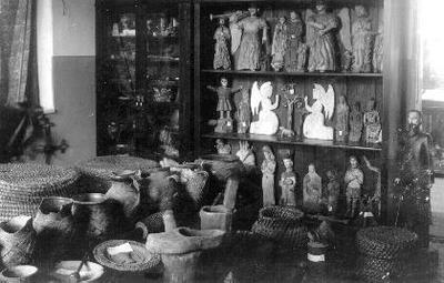Siužetinė. Biržų muziejaus, įsikūrusio Rotušės g., etnografijos ekspozicijos fragmentas: šventųjų skulptūra, geležinio kryžiaus viršūnė, bumblės, puodynės ir kt. Akiras - Biržys taip aprašo liaudies meno ekspoziciją: Vitrinoje po stiklu matyti daug smulkių liaudies meno išdirbinių: pypkių, tabakierkų, titnago skiltuvų, audinių, 6 galionai - vestuvininkų papuošalai