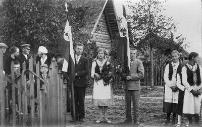 Siužetinė. Saločių (Pasvalio r.) Jaunųjų ūkininkų ratelio nariai šventinę dieną su vėliavomis. Jaunųjų ūkininkų rateliai Lietuvoje pradėti organizuoti 1929 m. Rateliams priklausęs jaunimas buvo teoriškai ir praktiškai ruošiamas ūkininkavimui.