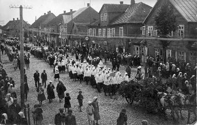 Siužetinė. Biržų katalikių moterų eisena Vytauto gatve, minint Lietuvos nepriklausomybės 20–ąsias metines. Kairė Vytauto g. pusė (einant nuo pašto). Eisena su gyvaisiais paveikslais. Tolumoje - kitų organizacijų atstovės. Pateikėjos Elenos Girčienės motina Pranė Pauliukienė (1900–1975) buvo katalikių moterų draugijos narė.