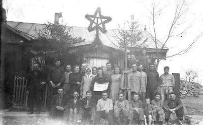 Siužetinė. Gegužės 1–osios šventės dalyviai prie nacionalizuoto Zivo malūno (?) kontoros Vabalninke (Biržų raj.). Prie pastato pritvirtinta žolynais apipinta penkiakampė žvaigždė, mergina laiko plakatą: .....Tarybų Sąjunga.....