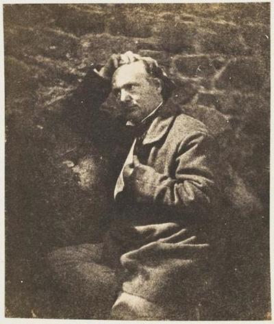 tirage photographique ; Victor Hugo assis devant un mur de pierres, profil gauche