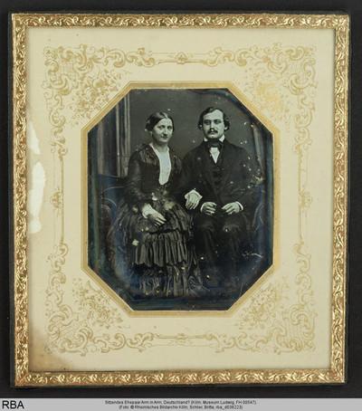 Sitzendes Ehepaar Arm in Arm