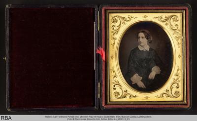 Portrait einer sitzenden Frau mit Haube