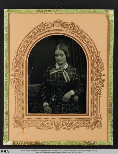 Portrait einer jungen Frau mit kariertem Kleid