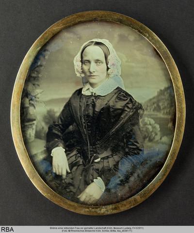 Bildnis einer sitzenden Frau vor gemalter Landschaft