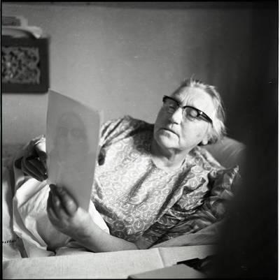 [Rašytoja Ieva Simonaitytė, žiūrinti į savo fotografiją. Vingio g. 11. Priekulė] / Bernardas Aleknavičius. - 1973.VI.16