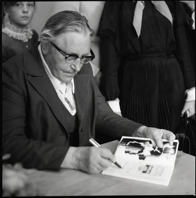[Rašytoja Ieva Simonaitytė, pasirašanti savo knygoje. Gargždai] / Bernardas Aleknavičius. - 1974.IX.21