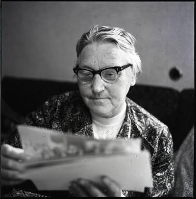 [Rašytoja Ieva Simonaitytė, žiūrinti į savo fotografijas. Švyturio g. 22-12. Vilnius] / Bernardas Aleknavičius. - 1974.IX.24