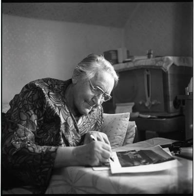 [Rašytoja Ieva Simonaitytė, pasirašanti ant savo fotografijos. Vingio g. 11. Priekulė] / Bernardas Aleknavičius. - 1976.X.3