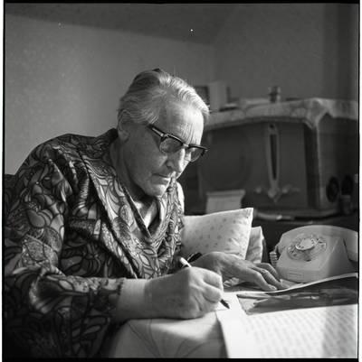 [Rašytoja Ieva Simonaitytė, paliekanti autografą. Vingio g. 11. Priekulė] / Bernardas Aleknavičius. - 1976.X.3