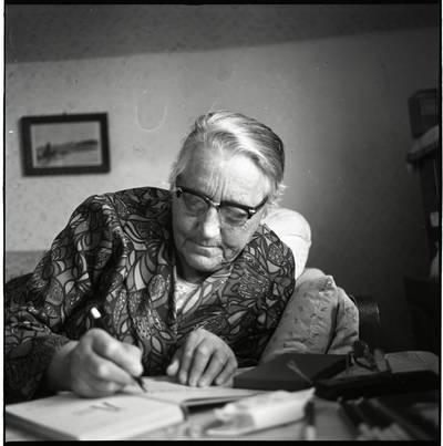 [Rašytoja Ieva Simonaitytė, pasirašanti savo knygoje. Vingio g. 11. Priekulė] / Bernardas Aleknavičius. - 1976.X.3