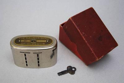 """Taupyklė, metalinė, originalioje popierinėje dėžutėje, su rakteliu. """"THE SAVINGS BANK OF GLASGOW No. 38065"""". 1900"""