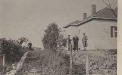 Nežinomas autorius. Nuotrauka. B. Sruoga, T. Reingardas, K. Penčyla ir nežinomas asmuo prie statomo namo. 1937-07-02