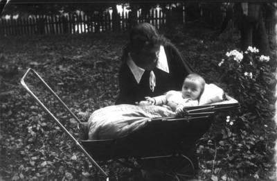 Fotografija.  Laimutė Valeikaitė vežimėlyje su savo prie jos pasilenkusia krikštamote. 1925