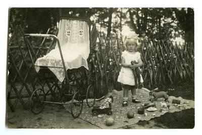 Danutė Adelė Markevičiūtė stovi lauke prie vežimėlio tarp savo žaislų. Kaunas, Lietuva, 1928 m.