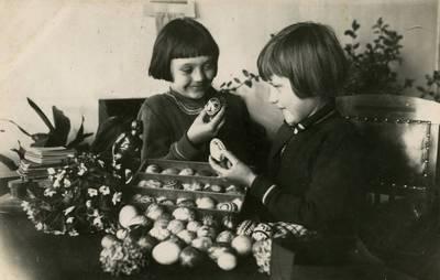 Garliavos pradžios mokyklos mokinė Laimutė Mitkaitė (kairėje) su drauge Danute apžiūri velykinius margučius. Garliava, Kauno apskr., Lietuva, apie 1936 m.