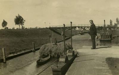 Karaliaus Vilhelmo kanalu plukdymui valtimi ruošiamas šienas. Tolumoje matyti Karaliaus Vilhelmo tiltas. Šilutės apskritis, Lietuva, 1936 m.