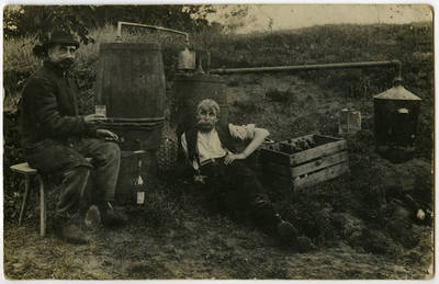 Du vyrai sėdi prie samanės virimo agregato. Lietuva, XX a. l p.
