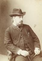 Mann mit Hut im Lehnstuhl sitzend