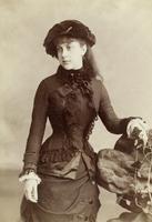 Junge Frau mit dunkler Haube und dunklem Kleid