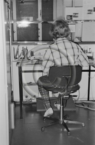 Nainen työskentelee työpöydän ääressä ilmeisesti Oy Wilh. Schauman Ab:n tehtaalla. Kuva liittyy ilmeisesti osapuun tehdasmittaukseen.