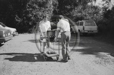 Kaksi miestä kuljettaa tietokonetta ja muita laitteita pysäköintialueella. Kuva liittyy puutavaran mittauksen anturiteknologian tutkimukseen?