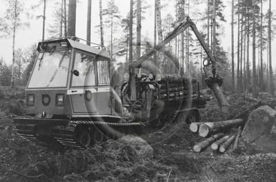Farmi Trac -telamaasturi puunkorjuussa. Puutavaraa kuormataan.