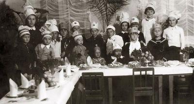 Vaikai prie Kalėdų stalo (centre sėdi Vytis, už jo stovi Rimgaudas Vaitkai). Kėdainiai, 1934 m. gruodžio 25