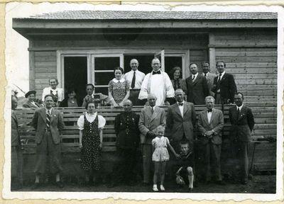 Grupinė nuotrauka prie namo (pirmas dešinėje – istorikas pedagogas Vincas Martinkėnas (1907–1997), trečias – Marcelinas Šikšnys, už jo – kunigas Kristupas Čibiras (1888–1942)). Lietuva (ne Vilniaus kraštas), galimai 1938 metai