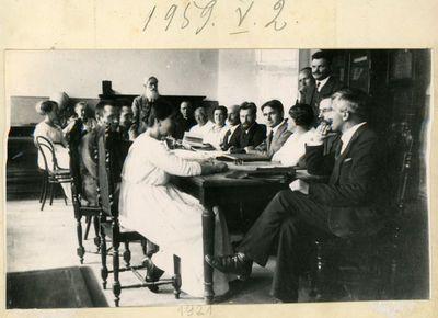 Pedagogų posėdis mokytojų seminarijoje (kalba Juozas Kairiūkštis, jam iš dešinės sėdi kunigas K. Čibiras, nežinomos moterys, M. Šikšnys, Viktoras Biržiška, Bronius Untulis, nežinomi moteris ir vyras, Vytautas Kairiūkštis. Vilnius, 1921 metai