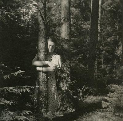 Gražutė Šlapelytė miške, apsikabinusi pušies kamieną
