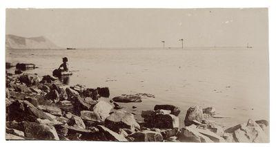 """Fotografija """"Akmenuotas jūros krantas ir sėdintis berniukas"""""""