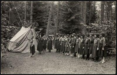 Skaučių rikiuotė prie palapinės stovykloje