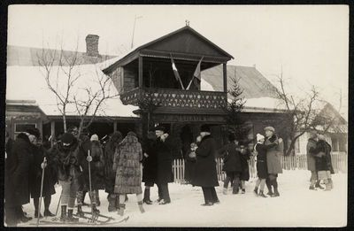 Žmonių grupė prisnigtame namo kieme šoka, slidinėja