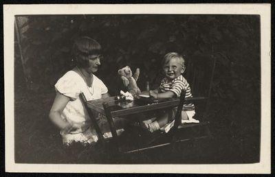 Moteris su vaiku žaidžia pievoje