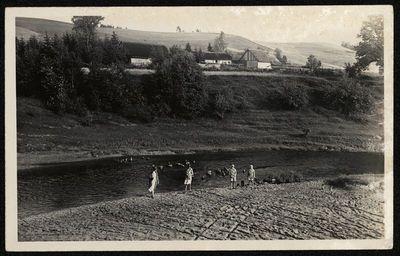 Moteris ir trys mergaitės prie upės
