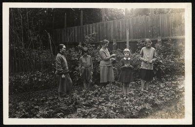 Dvi moterys ir trys mergaitės braškių lysvėje