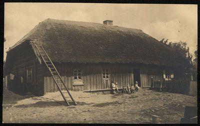 Vaikai prie medinio namo