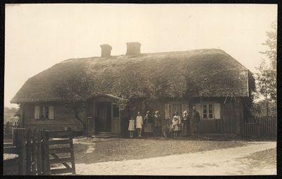 Žmonių grupė prie medinio namo